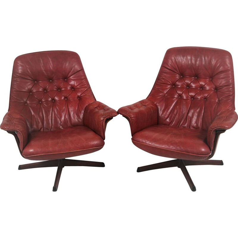 Pair of vintage leather swivel armchairs with wood accents and red leather upholstery 1960