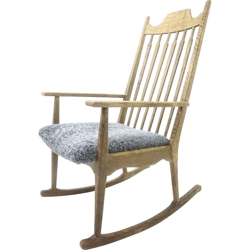 Mid-century rocking chair in solid oakwood with lamb wool upholstery by Henning Kjærnulf